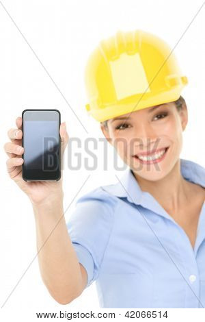 Engineer or architect woman showing smart mobile phone copy space. Young female professional smiling friendly and happy wearing yellow hard hat isolated on white background. Multicultural woman.
