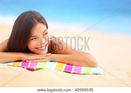 Relaxing beach woman smiling happy looking to the side. Beautiful girl sunbathing under summer sun lying in sand on beach with blue water. Mixed race Asian Chinese / Caucasian female model.