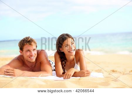 Couple on beach looking happy during summer travel vacation holidays. Multiracial young couple lying in sand on beach on looking to side. Asian woman, Caucasian man.