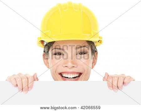 Construction worker / engineer woman showing sign wearing yellow hard hat. Happy young woman holding and peaking over white blank billboard sign card isolated on white background. Multiracial woman.