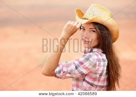 Young american cowgirl woman portrait outdoors. Beautiful natural woman saying hello looking at camera touching cowboy hat. Multicultural Caucasian / Asian girl in her twenties outdoor in nature.