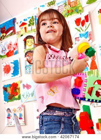 Child play block in play room. Preschool.