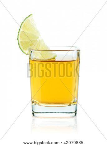 Caballito de tequila oro con una rodaja de limón. Aislado sobre fondo blanco