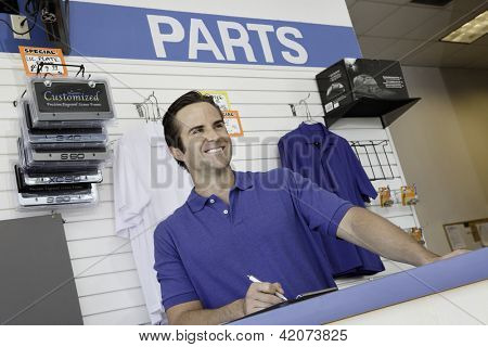 Male car mechanic standing at counter
