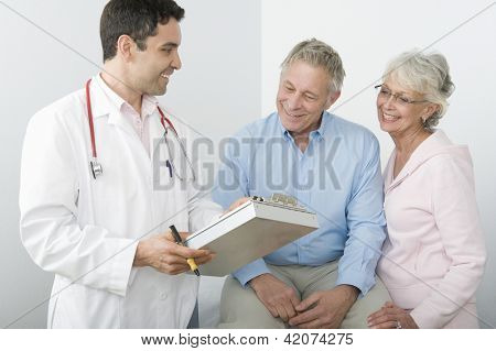 Male doctor showing reports to senior couple in clinic