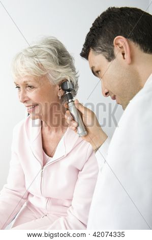 Male doctor checking patient's ear using otoscope