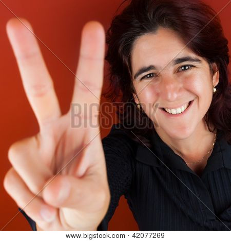 Happy hispanic woman in her thirties doing the victory sign with her fingers on a bright red background