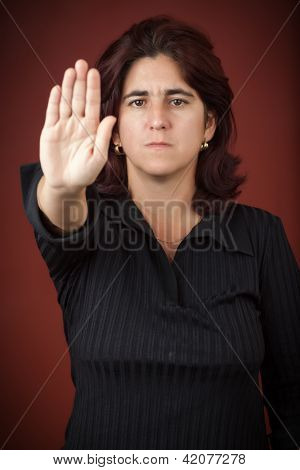 Serious hispanic woman with her hand extended signaling to stop (useful to campaign against violence or discrimination)