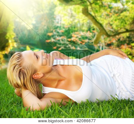 Beautiful healthy Young Woman relaxing on the green grass. Spring Beauty outdoor