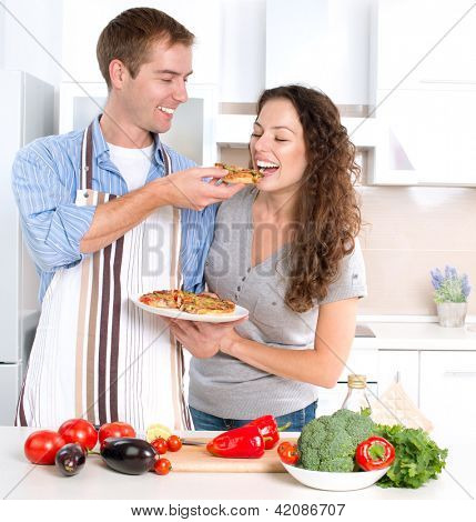 Happy Couple Eating Pizza. Cooking Together. Homemade Pizza. Smiling Family in the kitchen Preparing And Tasting Food