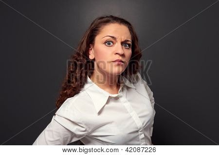studio shot of curly woman looking at camera. picture over dark background