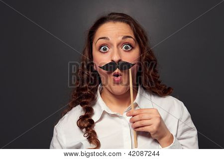 amazed woman with fake mustache. picture over dark background