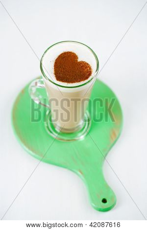 coffee latte with frothy milk in tall glass, rustic style, white and green wood