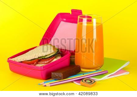 Lunch box with sandwich,juice and stationery on yellow background