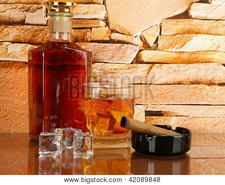 Bottle and Glass of whiskey and cigar on brick wall background