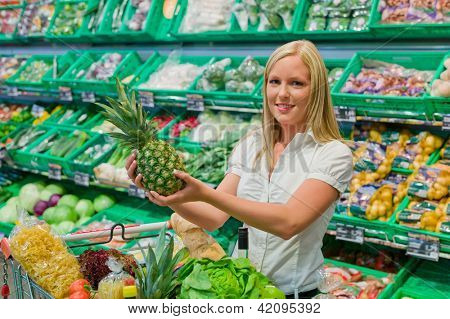 woman shopping for fruit and vegetables in a supermarket shelf freshness