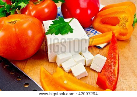 Feta cheese with vegetables on the board