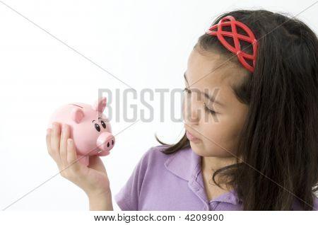 Asian Girl Looking At Piggy Bank