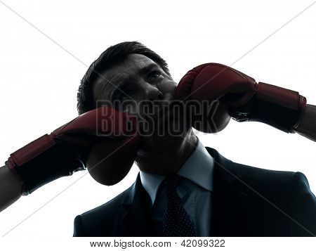 one caucasian businessman punch by boxing gloves  in silhouette studio isolated on white background