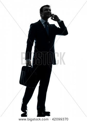 one caucasian businessman walking on the telephone in silhouette studio isolated on white background