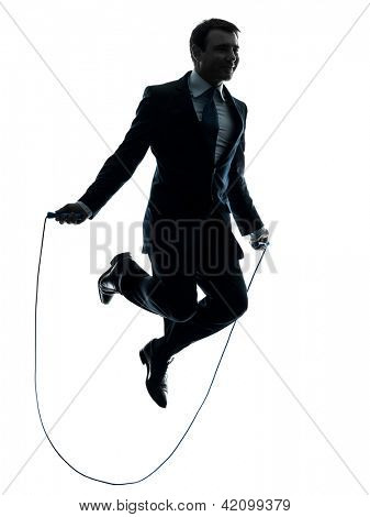 one caucasian businessman exercising jumping rope in silhouette studio isolated on white background