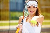 Young female tennis player offering you the ball
