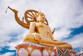 stock photo of sanctification  - Golden statue of Buddha sitting with beautiful skies above - JPG