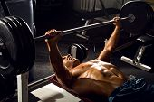 stock photo of execution  - very power athletic guy execute exercise press with weight in sport hall - JPG