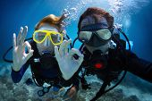stock photo of under sea  - Underwater shoot of a young couple diving with scuba in a tropical sea and showing ok signal - JPG