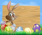 stock photo of wooden basket  - A cute Easter bunny rabbit character standing by a wooden sign holding a basket of decorated Easter eggs surrounded by Easter eggs in a field - JPG