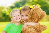 Photo two cute child hugging outdoors, brother and sister having fun on backyard in spring, nice lit