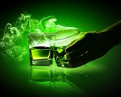 pic of absinthe  - Hand holding one of two glasses of green absinthe with fume going out - JPG