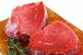 red raw fillet chops : three fresh beef meat chops with thyme twig on wooden plate . isolated over w