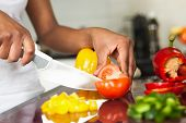 image of brazilian food  - African American womans hand slicing a tomatoe - JPG