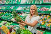 stock photo of local shop  - woman shopping for fruit and vegetables in a supermarket shelf freshness - JPG