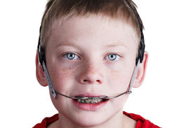picture of overbite  - Happy young boy wearing braces and headgear on white background - JPG