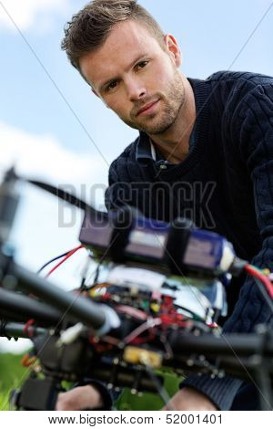 Closeup portrait of young engineer with UAV helicopter in park