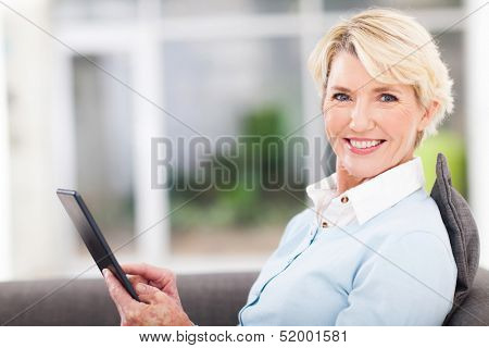 elegant middle aged woman using tablet pc at home