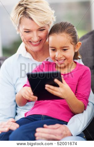 cute little girl using tablet pc with grandma at home