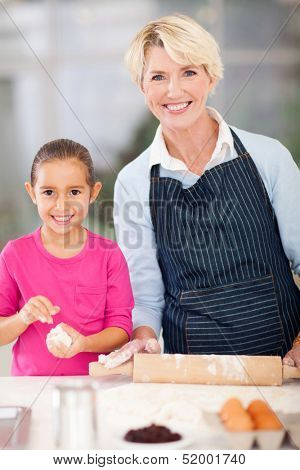 pretty little girl with her granny baking cookies at home