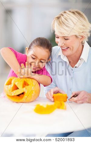 excited little girl cleaning her halloween pumpkin with granny at home