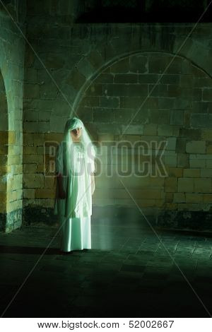 Night scene in a medieval castle with a woman ghost