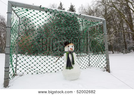 Funny snowman defending the soccer goal in the park