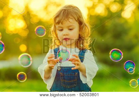 Sweet child child trying to catch soap bubble