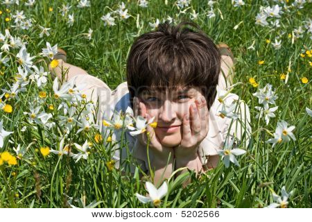 Woman Leaning On Her Elbows In Green Grass