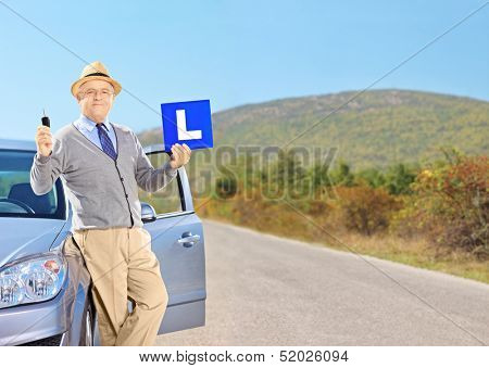 Happy senior man posing on his car, holding a L sign and car key after having his driver's licence on an open road, shot with a tilt and shift lens