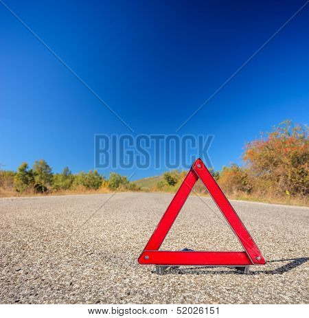 View of a red warning triangle on a road, shot with a tilt and shift lens