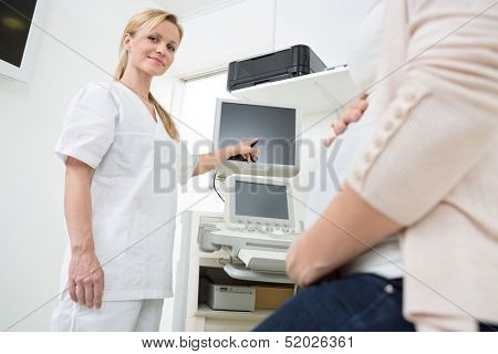 Portrait of young gynecologist showing ultrasound scan to pregnant woman in clinic