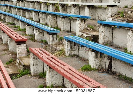 Long dirty destroyed blue and red grandstands and staircase at old stadium.