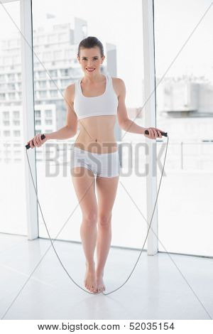 Playful fit brown haired model in sportswear using a skipping rope in bright fitness studio